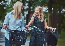 El retrato de una madre y la hija con un pelo rubio en una bicicleta montan con su pequeño perro lindo del perro de Pomerania en  Fotografía de archivo