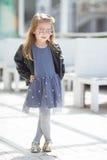 El retrato de una moda que lleva de la niña pequeña adorable viste Fotos de archivo