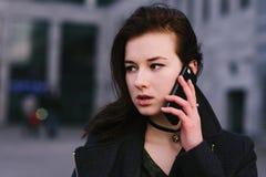 El retrato de una morenita hermosa y seria joven de la mujer de negocios está hablando en el teléfono en una ciudad un fondo oscu Foto de archivo