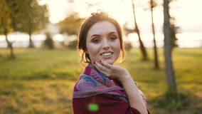 El retrato de una morenita joven liga en la cámara con sus ojos en parque soleado del otoño almacen de video