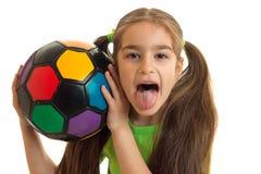 El retrato de una muchacha alegre con un balón de fútbol muestra el tonque Imagenes de archivo