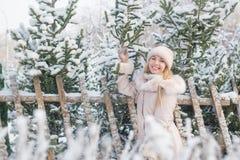 El retrato de una muchacha bonita sonriente en una chaqueta beige coloca cerca de piceas en un día de invierno fotografía de archivo