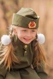El retrato de una muchacha con dos trenzas y blancos arquea en uniforme en Victory Day Foto de archivo