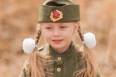 El retrato de una muchacha con dos trenzas y blancos arquea en uniforme en Victory Day Imágenes de archivo libres de regalías