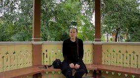 El retrato de una muchacha con la trenza se vistió en la sentada negra en el gazebo en verano metrajes