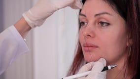 El retrato de una muchacha, cosmetólogo alinea la forma de las cejas con la ayuda del hilo teñido 4K MES lento metrajes