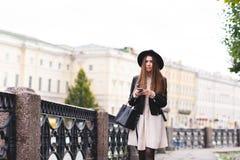 El retrato de una muchacha elegante del inconformista se vistió en la ropa fresca que presentaba en la calle mientras que teléfon Fotografía de archivo