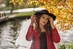 El retrato de una muchacha en sombrero negro con un río en un fondo que refleja el ` s del sol irradia y los árboles amarillos de fotografía de archivo