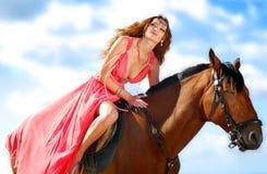 El retrato de una muchacha en un caballo con una playa Imagen de archivo libre de regalías