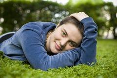 El retrato de una muchacha hermosa con el pelo corto y los ojos verdes miente en la hierba, sonriendo y mirando la cámara Imagen de archivo
