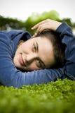 El retrato de una muchacha hermosa con el pelo corto y los ojos verdes miente en la hierba, sonriendo y mirando la cámara Fotos de archivo
