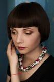 El retrato de una muchacha hermosa con el pelo de la sacudida del collar y del pelo se endereza y mira abajo Imágenes de archivo libres de regalías