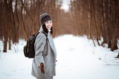 El retrato de una muchacha hermosa feliz con el pelo marrón en el bosque del invierno se vistió en un estilo del inconformista, f imágenes de archivo libres de regalías