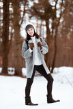 El retrato de una muchacha hermosa feliz con el pelo marrón en el bosque del invierno se vistió en un estilo del inconformista, f imagenes de archivo