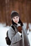 El retrato de una muchacha hermosa feliz con el pelo marrón en el bosque del invierno se vistió en un estilo del inconformista, f fotografía de archivo libre de regalías