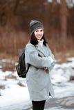 El retrato de una muchacha hermosa feliz con el pelo marrón en el bosque del invierno se vistió en un estilo del inconformista, f imagen de archivo