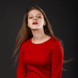 El retrato de una muchacha hermosa joven con los ojos se cerró en un dre rojo Foto de archivo libre de regalías