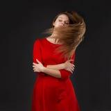 El retrato de una muchacha hermosa joven con los ojos se cerró en un dre rojo Imagen de archivo libre de regalías