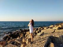 El retrato de una muchacha hermosa joven contra el mar Silueta del hombre de negocios Cowering Crete, Grecia imagen de archivo libre de regalías