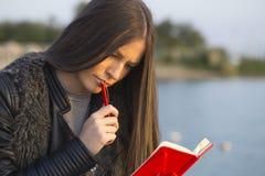 El retrato de una muchacha hermosa mientras que localiza por el mar y escribe Fotografía de archivo