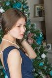 El retrato de una muchacha linda en un fondo adornó el árbol de navidad Imagen de archivo