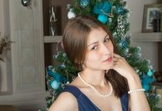 El retrato de una muchacha linda en un fondo adornó el árbol de navidad Fotos de archivo