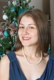 El retrato de una muchacha linda en un fondo adornó el árbol de navidad Imagen de archivo libre de regalías