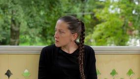 El retrato de una muchacha pensativa con la trenza se vistió en la sentada negra en el gazebo almacen de video