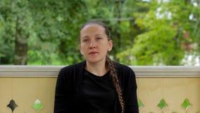 El retrato de una muchacha sonriente con la trenza se vistió en la sentada negra en el gazebo metrajes