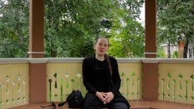El retrato de una muchacha sonriente con la trenza se vistió en la sentada negra en el gazebo almacen de video