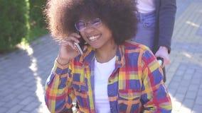 El retrato de una mujer afroamericana joven sonriente positiva inhabilitó en una silla de ruedas que hablaba en el teléfono almacen de video