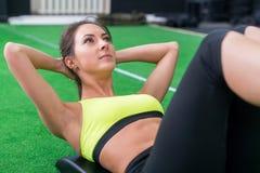 El retrato de una mujer atlética que hace ejercitando abdominals resuelve la mentira en gimnasio Fotografía de archivo