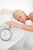 El retrato de una mujer cansada despierta por un reloj de alarma imágenes de archivo libres de regalías