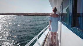 El retrato de una mujer caucásica atractiva hermosa joven en un yate adentro en un vestido azul y gafas de sol invita para viajar almacen de video