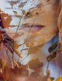 El retrato de una mujer con una exposición doble, la muchacha y la naturaleza borrosa de la foto no está en foco Las hojas en la  fotos de archivo