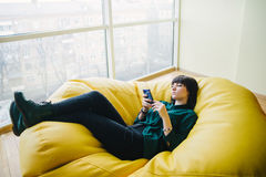 El retrato de una mujer de negocios elegante joven hermosa que miente en un bolso de la silla y utiliza el teléfono Rotura en la  Foto de archivo libre de regalías