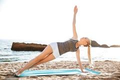 El retrato de una mujer feliz que hace yoga ejercita en la estera Imagen de archivo libre de regalías