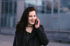 El retrato de una mujer feliz y elegante vestida está hablando en el teléfono en una ciudad un fondo oscuro Fotos de archivo