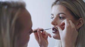 El retrato de una mujer hermosa, lápiz labial pinta un color oscuro, mirando en el espejo Pinturas hermosas atractivas de una muc almacen de metraje de vídeo