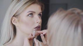 El retrato de una mujer hermosa, lápiz labial pinta un color oscuro, mirando en el espejo Pinturas hermosas atractivas de una muc almacen de video