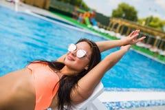 El retrato de una mujer hermosa que presenta por la piscina, día de verano, al aire libre se relaja imagenes de archivo