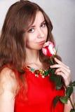 El retrato de una mujer joven hermosa con un rojo se levantó Fotos de archivo
