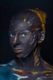 El retrato de una mujer joven que está presentando cubrió con la pintura negra Imagen de archivo libre de regalías