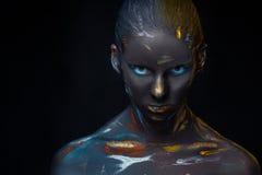 El retrato de una mujer joven que está presentando cubrió con la pintura negra Fotografía de archivo libre de regalías