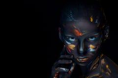 El retrato de una mujer joven que está presentando cubrió con la pintura negra Imagenes de archivo