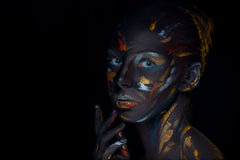 El retrato de una mujer joven que está presentando cubrió con la pintura negra Imágenes de archivo libres de regalías