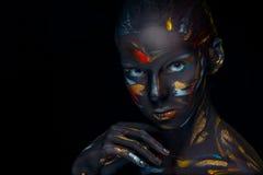 El retrato de una mujer joven que está presentando cubrió con la pintura negra Imagen de archivo