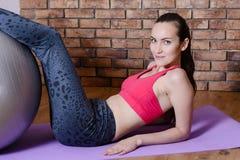 El retrato de una mujer joven realiza un ejercicio en los músculos abdominales, levantando el torso para arriba Aptitud casera Fotos de archivo