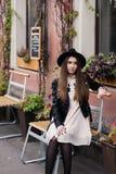 El retrato de una mujer joven se vistió en la ropa de moda fresca que se sentaba en una silla de la calle cerca del edificio con  Fotografía de archivo libre de regalías