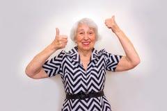 El retrato de una mujer mayor alegre que gesticula la victoria sobre rosa Foto de archivo libre de regalías